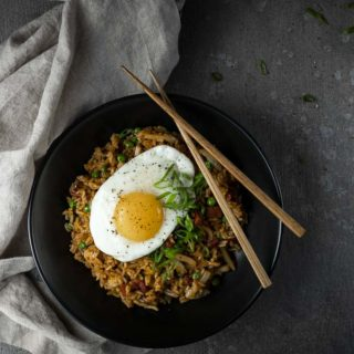 bowl of fried rice topped with an egg and sliced green onions with chopsticks
