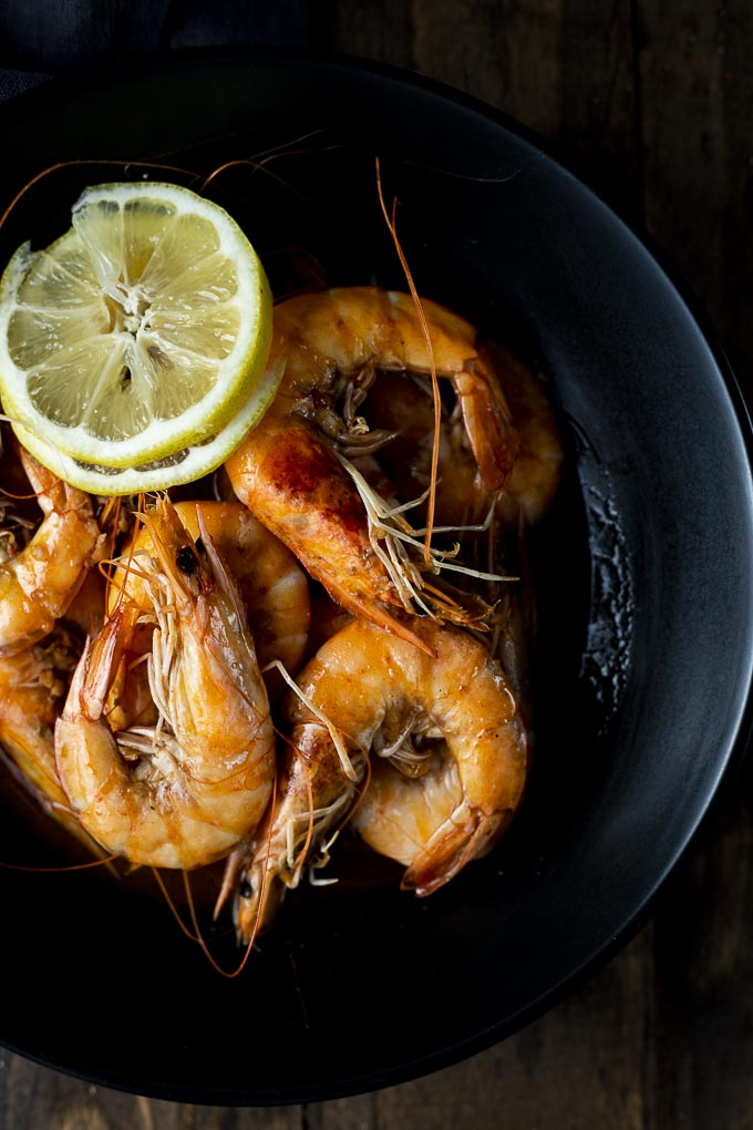 head on shrimp in a bowl with lemon slices