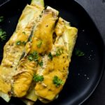 squash in a cheesy sauce on a plate garnished with parsley