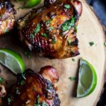 roasted chicken thighs garnished with cilantro and fresh limes