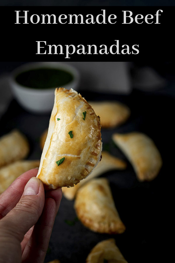 These Beef Empanadas are filled with ground beef, vegetables & spices, wrapped up in pie crust, baked until browned & crispy, & served with chimichurri. Learn how to make empanadas in just a few easy steps. Using pre-made pie crust makes this beef empanada recipe super easy to make and addictively delicious! #wenthere8this #beefempanadas #argentinianempanadas #bakedempanada