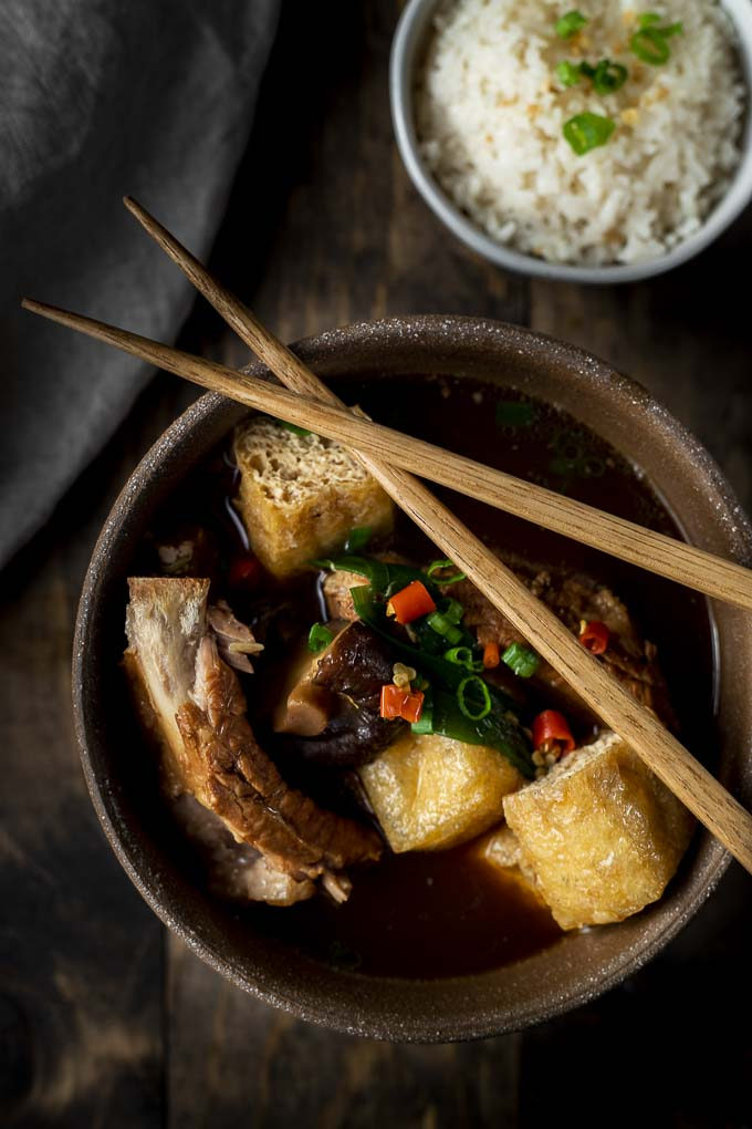 ribs, tofu, mushroom, chilies and green onions in broth with chopsticks