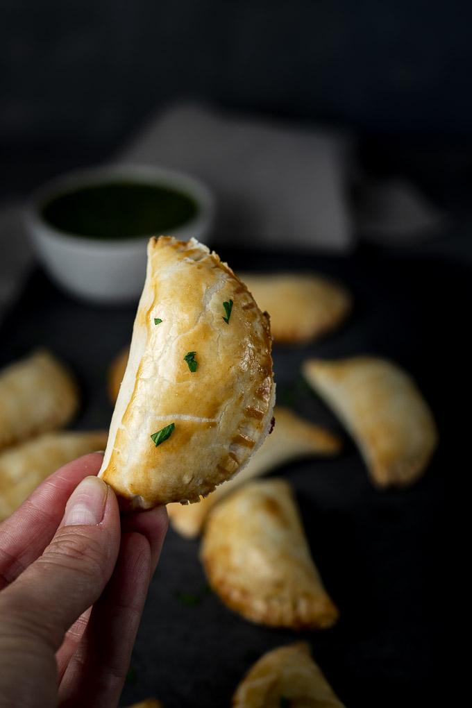 a hand holding an empanada