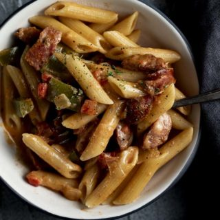 bowl of pasta with peppers, onions and sausage in a cream sauce