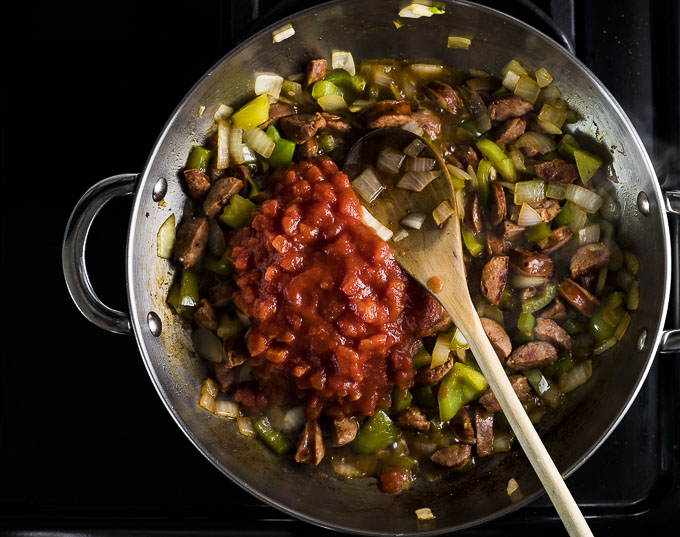 sausage and vegetables with tomatoes in a skillet