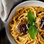 meatballs and pasta in creamy red pepper pesto sauce in a bowl