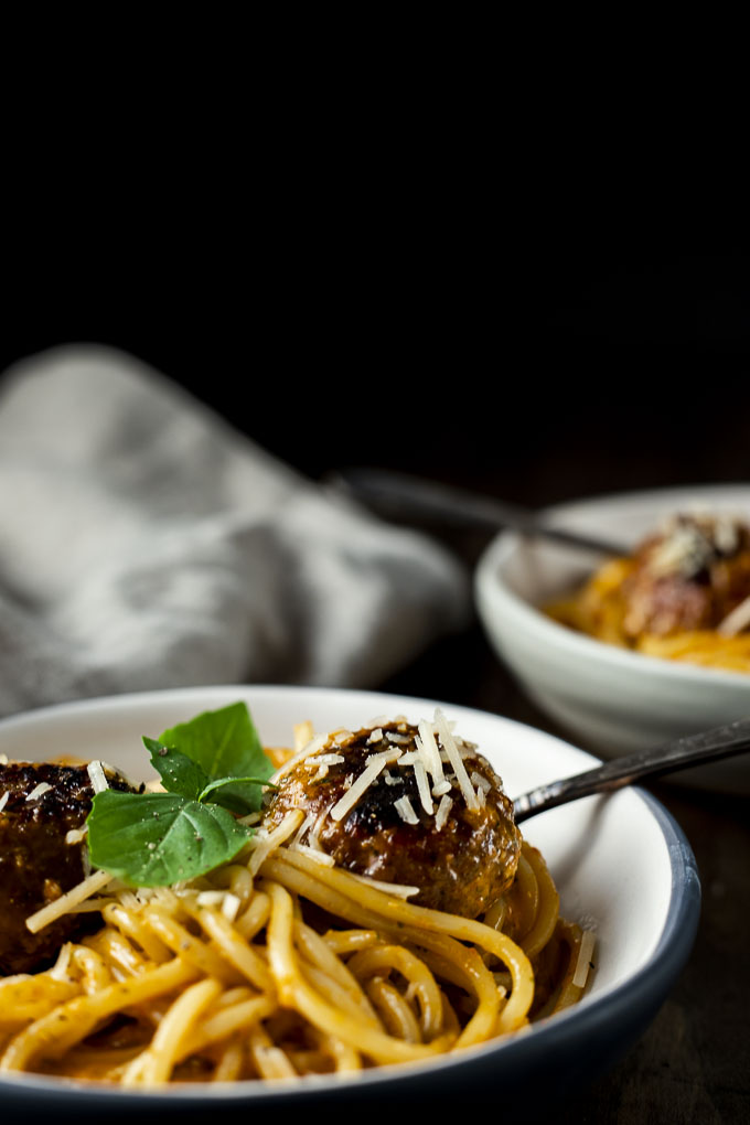 bowl of pasta in orange sauce with meatballs
