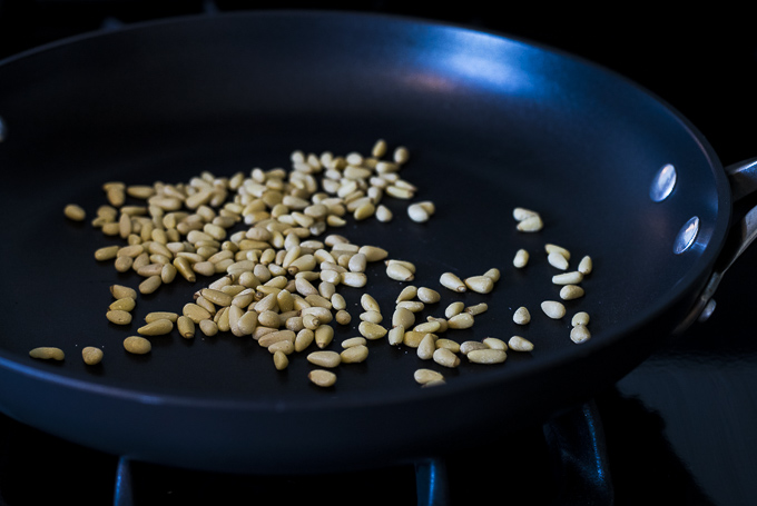 pine nuts toasting in a skillet