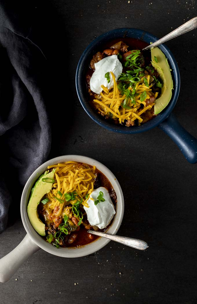 2 bowls of chili with cheese, sour cream and avocado