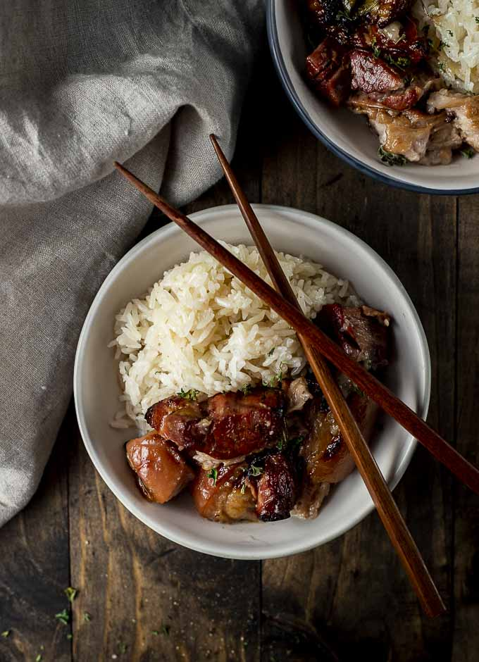 bowl of rice and pork belly with chopsticks