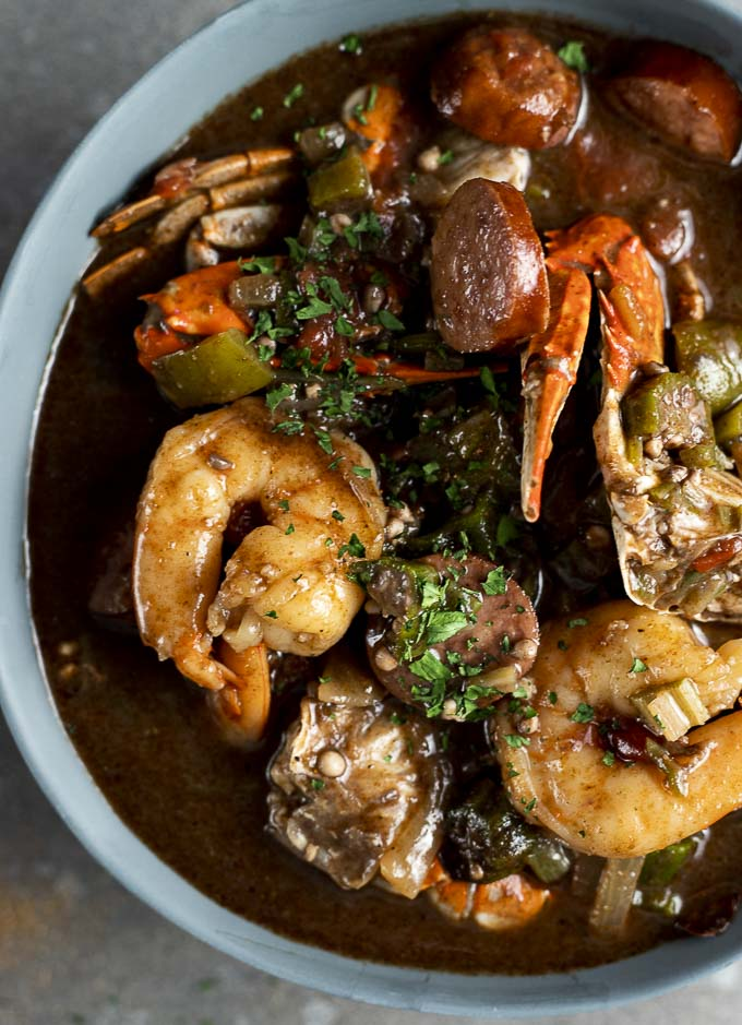a bowl of gumbo with crab, shrimp, sausage and vegeatbles