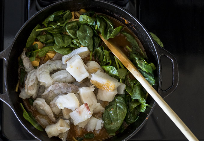 raw seafood and spinach added to a pot of simmering orange broth