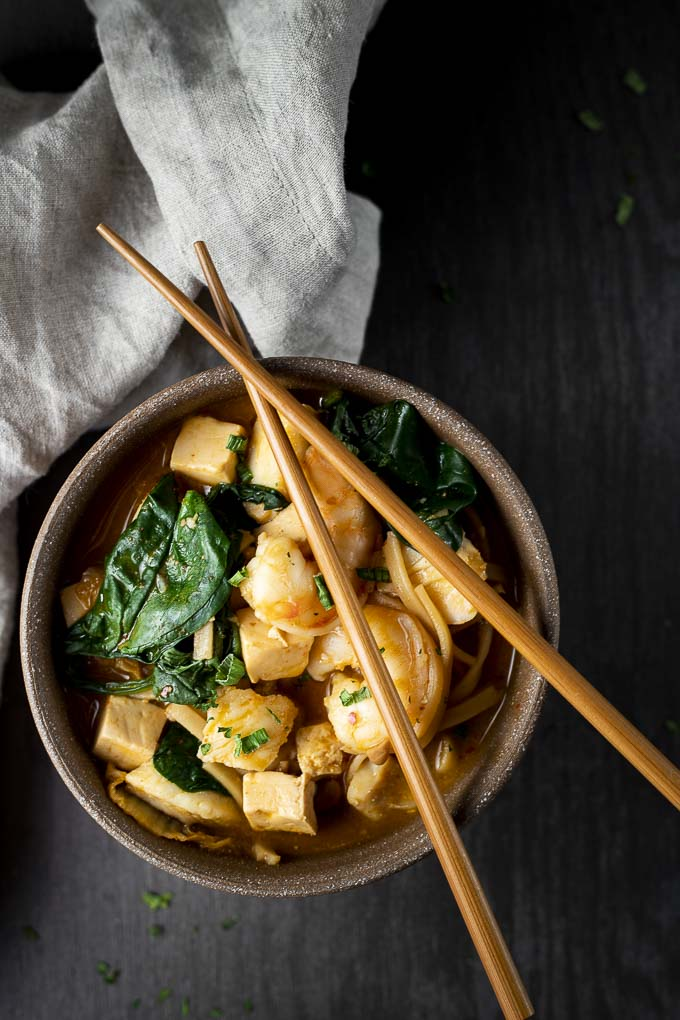 spicy kimchi stew in a bowl with spinach and chopsticks