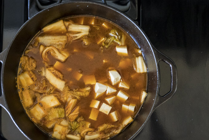 orange colored stew with tofu, vegetables, kimchi and seafood