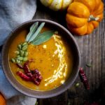 bowl of orange soup with pumpkin seeds, chilies and sage