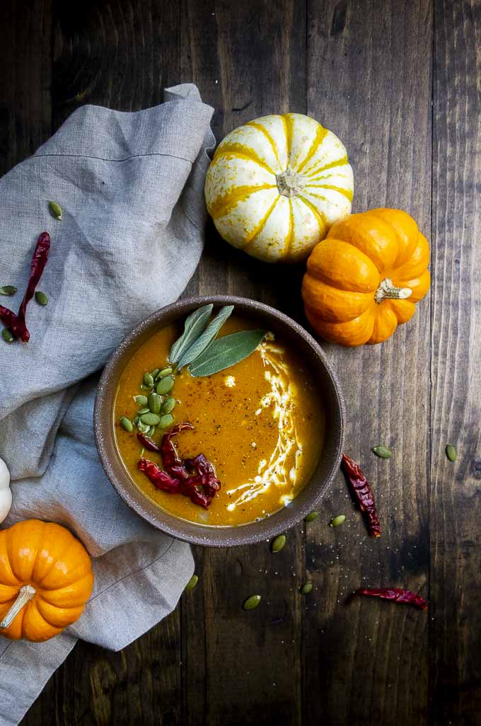 bowl of pumpkin soup with mini pumpkins on the side