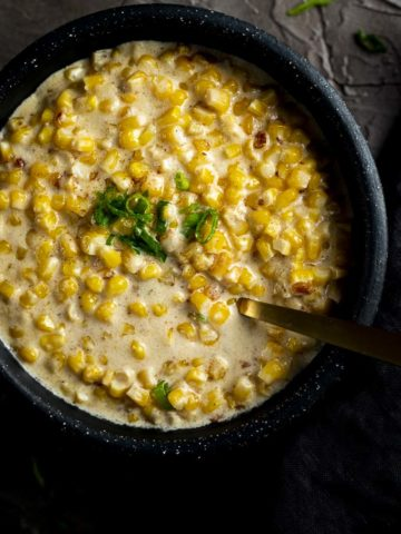 creamed corn in a bowl garnished with green onions