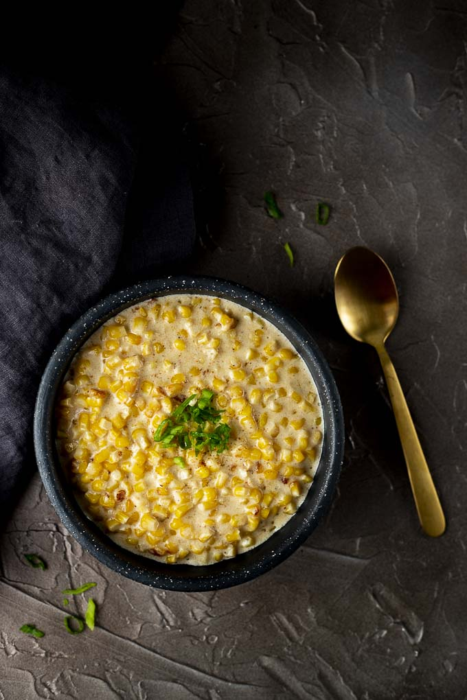 bowl of creamed corn with spoon on the side