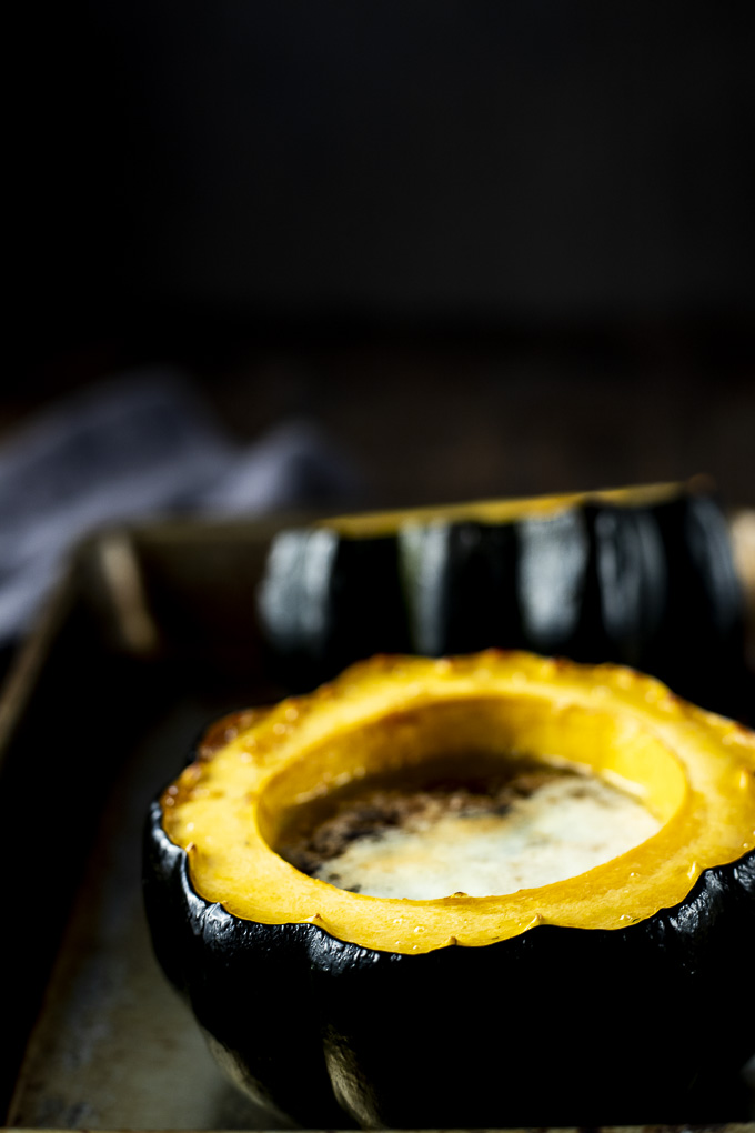 roasted acorn squash half with melted butter in middle - side view