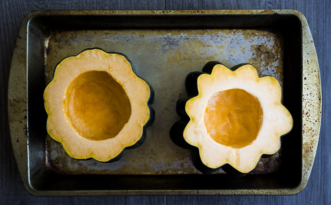 acorn squash cut in half on a baking sheet