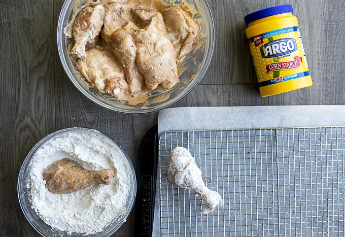 marinated chicken being coated with flour