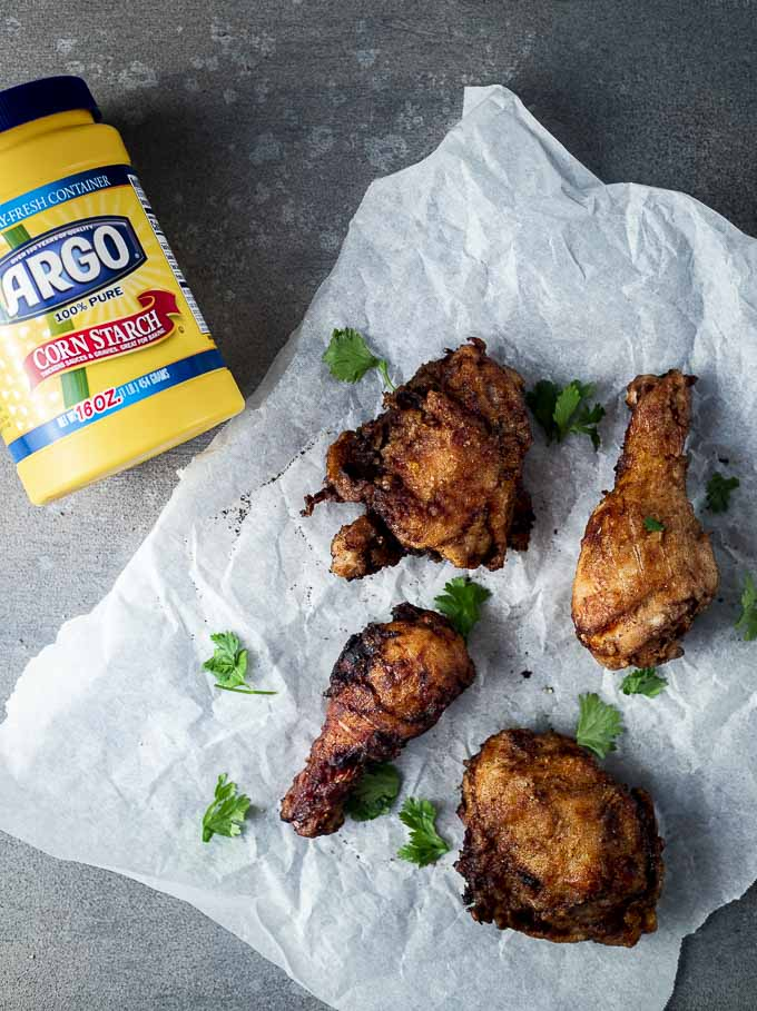 4 pieces of fried chicken on parchment paper with a container of cornstarch