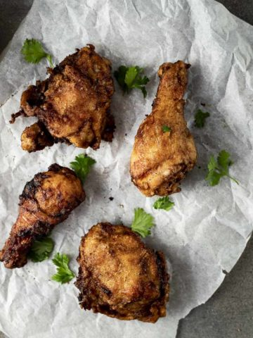 fried chicken on pasrchment paper garnished with cilantro
