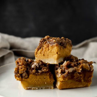 side view of 3 pumpkin pie bars on a plate