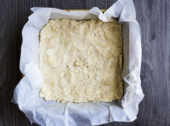 Dough spread on parchment paper in a square pan