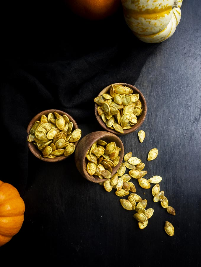 bowls of roasted pumpkin seeds with one spilled