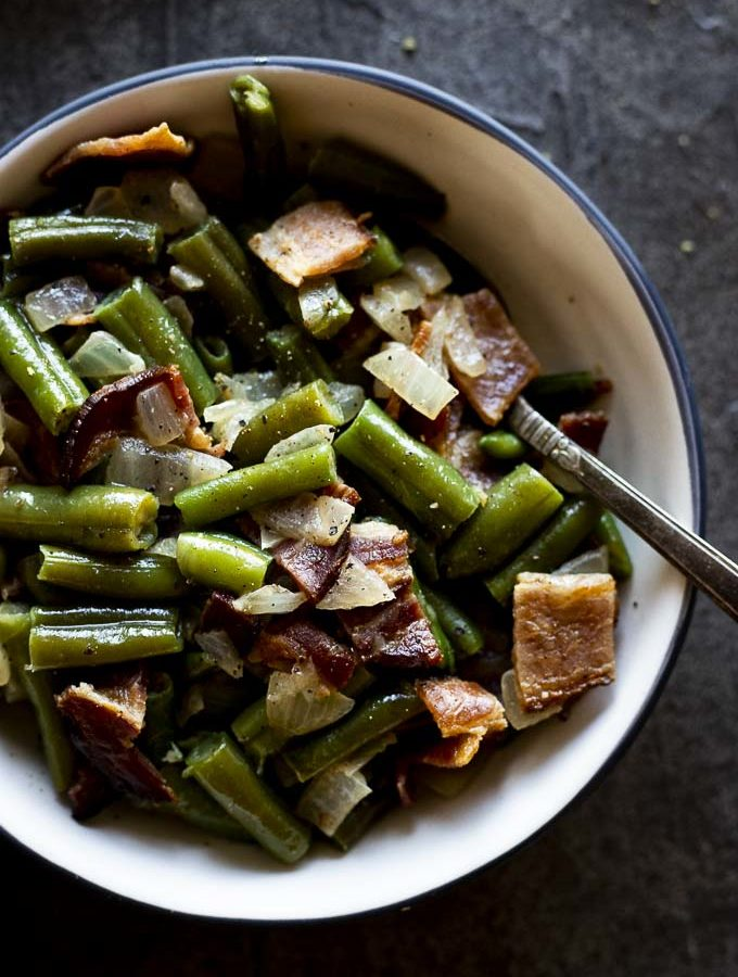 green beans mixed with bacon and onions in a bowl