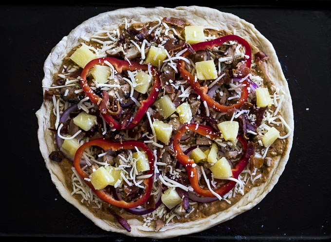 raw dough with pineapple, chicken, red peppers and onions on top