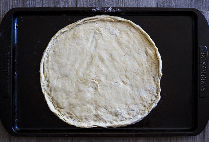 rolled out pizza dough on a baking sheet