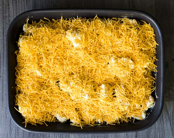 cauliflower topped with cheddar cheese in a baking dish