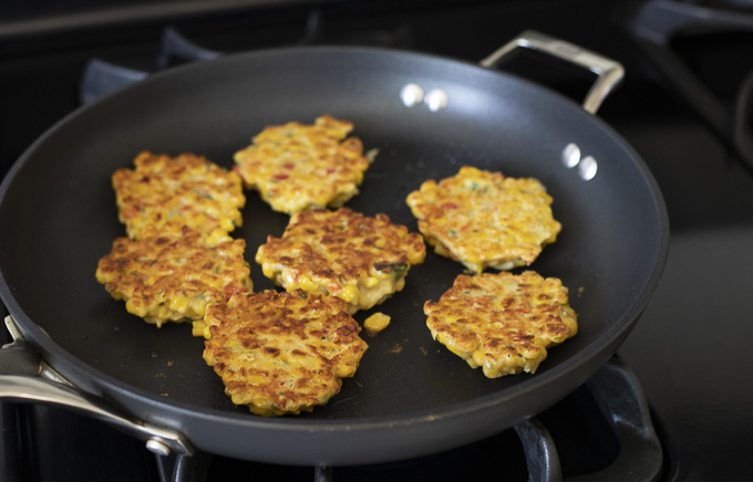 corn fritters being fried in a pan