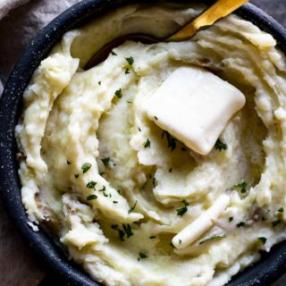 bowl of mashed potatoes with butter and a spoon