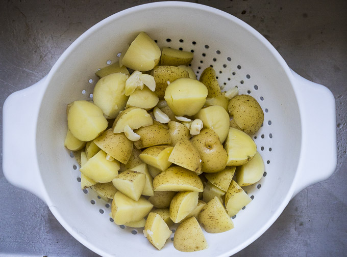 cooked diced potatoes in a colander