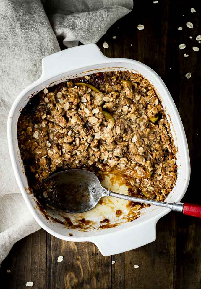 apple crisp in a baking dish with a serving spoon
