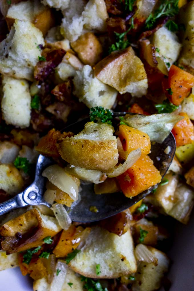 spoon full of bread stuffing with butternut squash and vegetables