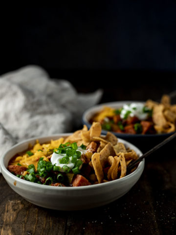 2 bowls of chili with fritos garnished with green onions