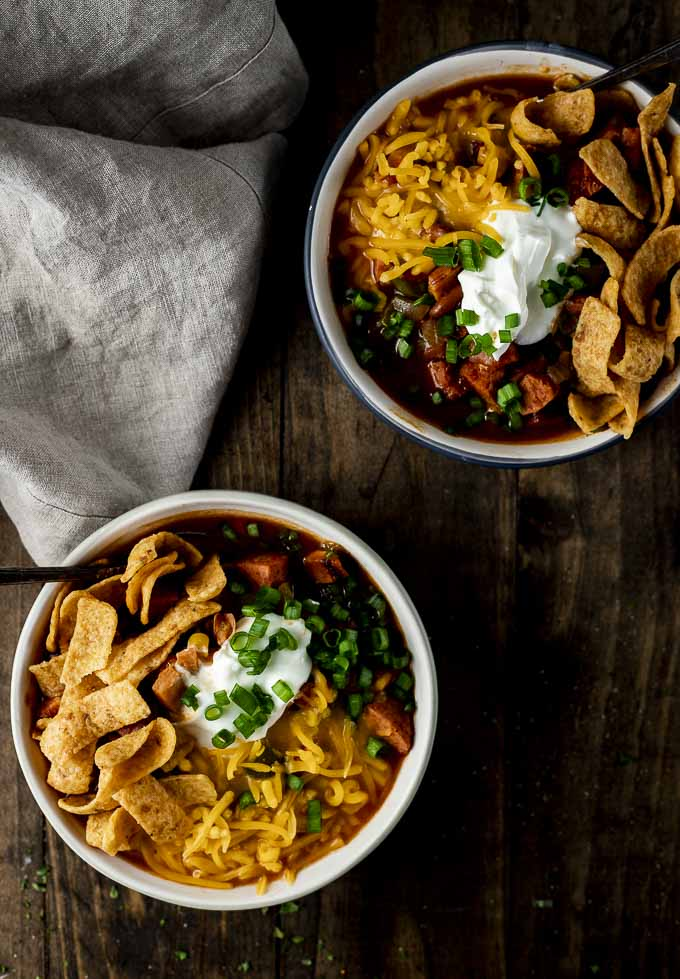 2 bowls of chili with sour cream, green onions, cheese and corn chips