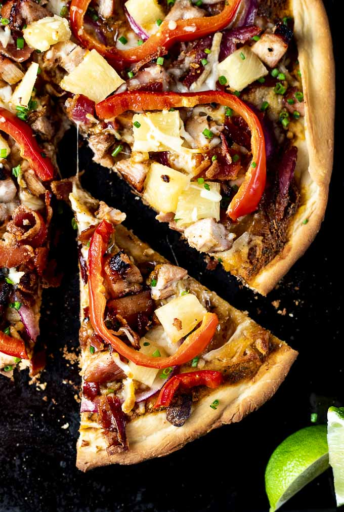 slice of pizza with red peppers, chicken and pineapple