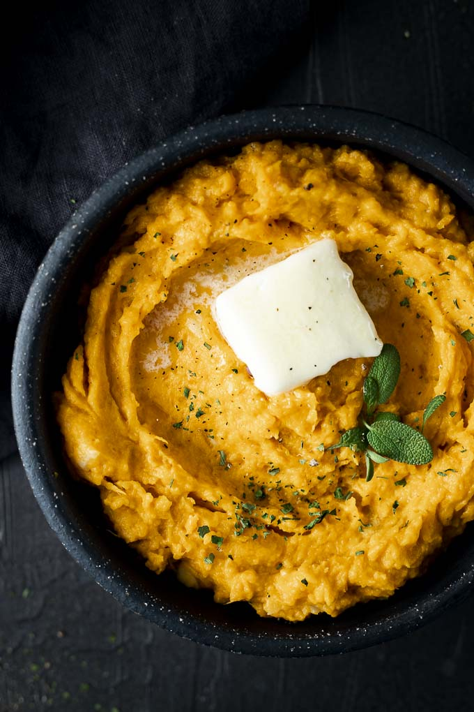 bowl of mashed sweet potatoes with butter and fresh sage