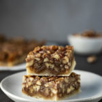 2 pecan pie bars stacked on a plate