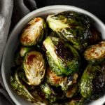 bowls of spicy roasted brussels sprouts with charred edges