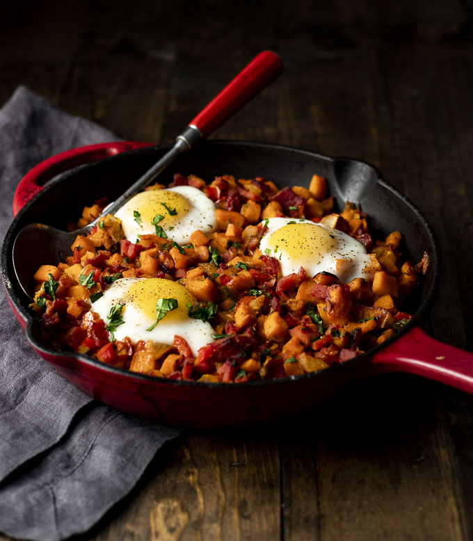 sweet potato hash in a skillet with a spoon