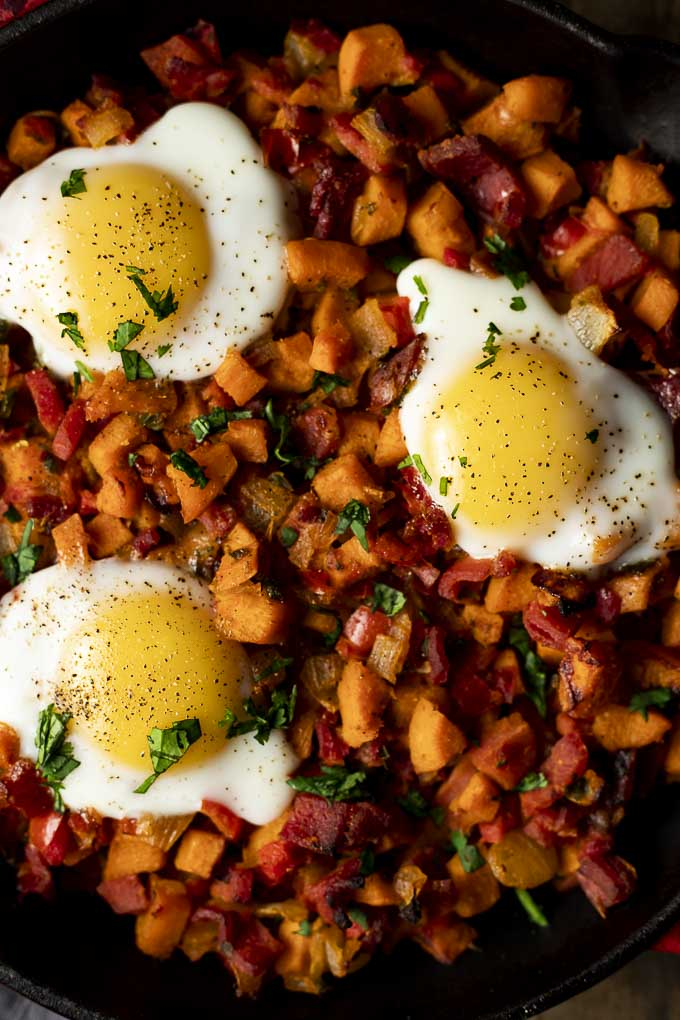 close up sweet potato hash in a skillet with eggs