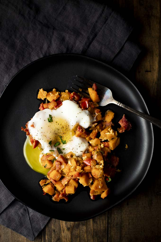 sweet potato hash on a plate with an egg