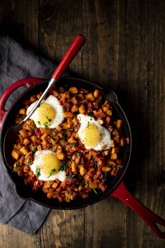 skillet of sweet potato hash with eggs on top