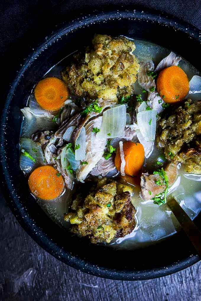 3 stuffing balls, carrots and turkey in a bowl of broth